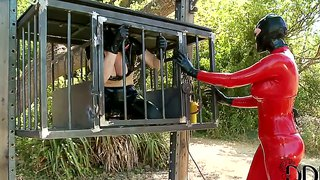 A Latex-Clad Mistress Has Her Sub In A Cage